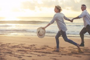 Mature couple running and playing on the beach at sunset or sunrise.